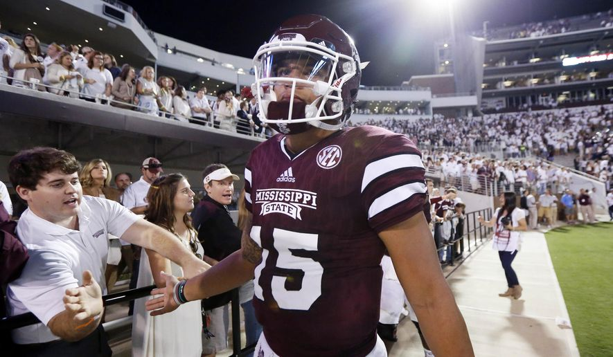 FILE - In this Saturday, Sept. 12, 2015, file photo, a disappointed Mississippi State quarterback Dak Prescott (15) slaps hands with fans after their loss to LSU in an NCAA college football game at Davis Wade Stadium in Starkville, Miss. Prescott has had a great start to the season throwing the football with 335 yards through the air in last weekend's lost to LSU. The bad news is he only has 53 yards rushing through the first two games, which is way off of last year's pace.  (AP Photo/Rogelio V. Solis, File)