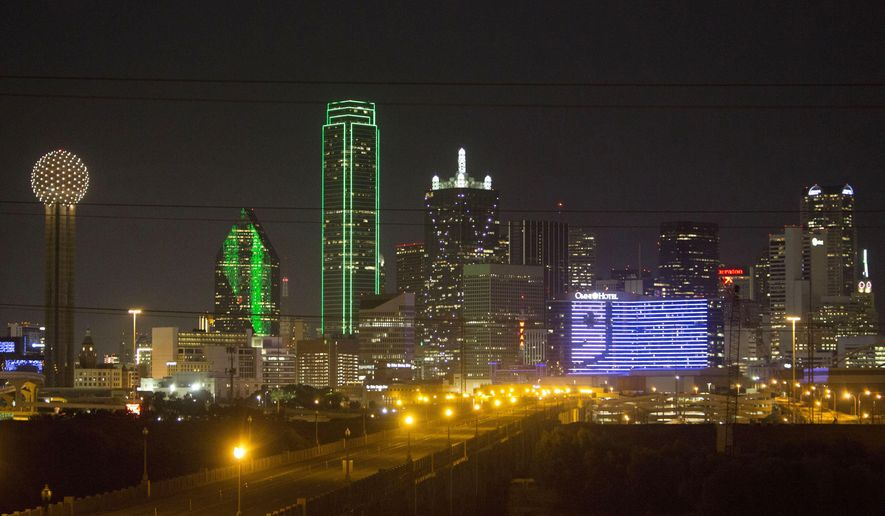 In this photo taken on Monday, Sept. 15, 2015, the Goodwill logo is illuminated on the Omni Dallas Hotel the night before Goodwill's 2015 First Annual Lunch, in Dallas. Over the last decade, Dallas commercial buildings have donned an increasingly elaborate wardrobe of high-tech lighting systems.   (David Guzman/The Dallas Morning News via AP) MANDATORY CREDIT; MAGS OUT; TV OUT; INTERNET USE BY AP MEMBERS ONLY; NO SALES