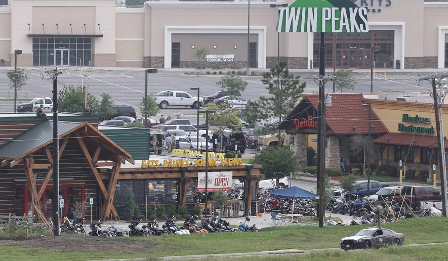 FILE - In this May 18, 2015 file photo, law enforcement continue to investigate the motorcycle gang related shooting at the Twin Peaks restaurant in Waco, Texas, where 9 were killed and over a dozen injured. Police shot bikers in the deadly shootout that erupted last spring outside a Texas restaurant, though it remains unclear if their bullets caused any of the nine fatalities, according to evidence reviewed by The Associated Press. (AP Photo/Jerry Larson, File)