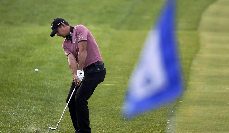 Jason Day of Australia, hits his approach shot to the ninth green to finish the rain postponed first round of the BMW Championship golf tournament at Conway Farms Golf Club, Friday, Sept. 18, 2015, in Lake Forest, Ill. (AP Photo/Charles Rex Arbogast)