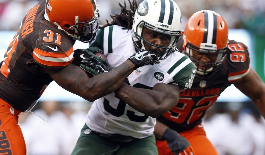 FILE - In this Sunday, Sept. 13, 2015, file photo, New York Jets running back Chris Ivory (33) is tackled by Cleveland Browns' Donte Whitner (31) during the second half of an NFL football game in East Rutherford, N.J. The  Jets running back is a powerful, physical presence who approaches each carry in a game as if it might be his last. (AP Photo/Kathy Willens, File0a