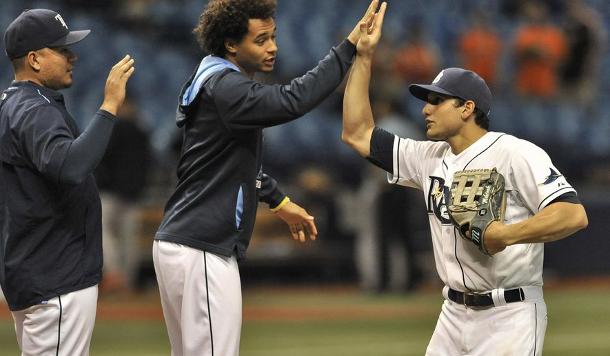 Tampa Bay Rays' Erasmo Ramirez, left, Chris Archer, center, and Mikie Mahtook celebrate a 8-6 win over the Baltimore Orioles during a baseball game Friday, Sept. 18, 2015, in St. Petersburg, Fla. Mahtook went five for five at the plate, hitting two doubles and three singles. (AP Photo/Steve Nesius)