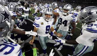 FILE - In this Sunday, Sept. 13, 2015, file photo, Dallas Cowboys quarterback Tony Romo (9) is greeted by the team before an NFL football game against the New York Giants in Arlington, Texas. Dogged for years about his failures in the clutch, Romo just might be changing the narrative on his career in his ninth full season as the starter. Romo has made big plays on big drives in three straight games going back to last year's playoffs. (AP Photo/Brandon Wade)