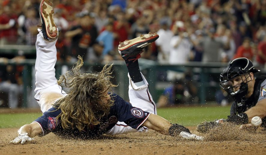Washington Nationals' Jayson Werth scores the winning run on a sacrifice fly by Jose Lobaton as Miami Marlins catcher J.T. Realmuto, right, can't hang onto the ball during the 10th inning of a baseball game at Nationals Park, Friday, Sept. 18, 2015, in Washington. The Nationals won 5-4. (AP Photo/Alex Brandon)