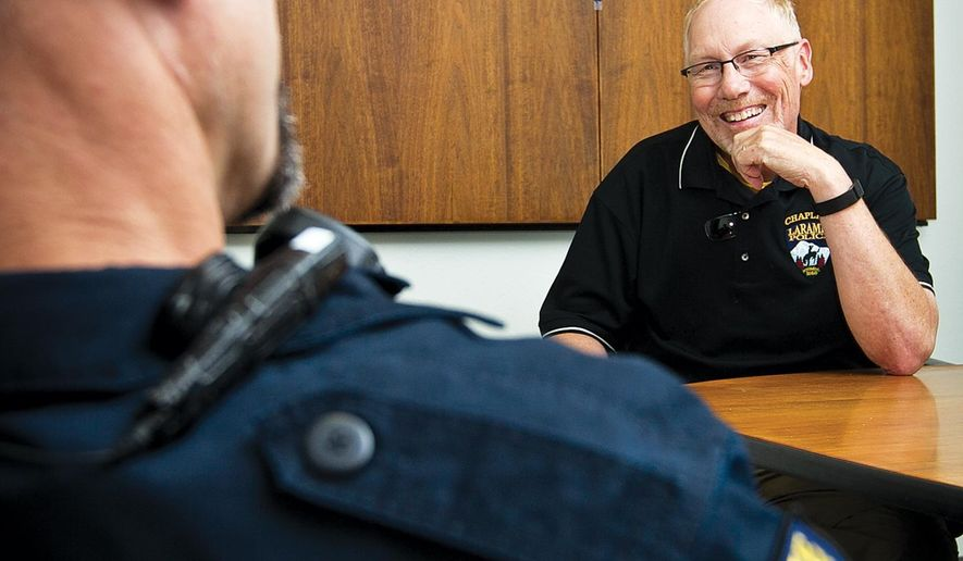 In this photo taken on Aug. 27, 2015, Laramie Police Department Chaplain Brad Eakins sits down for a conversation with LPD sergent Taun Smith in the LPD conference room, in Laramie, Wy. (Jeremy Martin/Laramie Daily Boomerang via AP) MANDATORY CREDIT