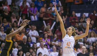 Tulsa Shock's Odyssey Sims (0) shoots over the defense of Phoenix Mercury's Brittney Griner during the opening game of a WNBA basketball Western Conference semifinal series, Thursday, Sept. 17, 2015, in Phoenix. (Patrick Breen/The Arizona Republic via AP)