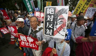 """Protesters holding """"No war"""" placards stage a rally against Japanese government in front of the parliament building in Tokyo, Friday, Sept. 18, 2015. Japan's parliament is moving toward final approval of legislation that would loosen post-World War II constraints placed on its military, an issue that has sparked sizable street protests and raised fundamental questions about whether the nation needs to shift away from its pacifist ways to face growing security challenges. (AP Photo/Koji Ueda)"""