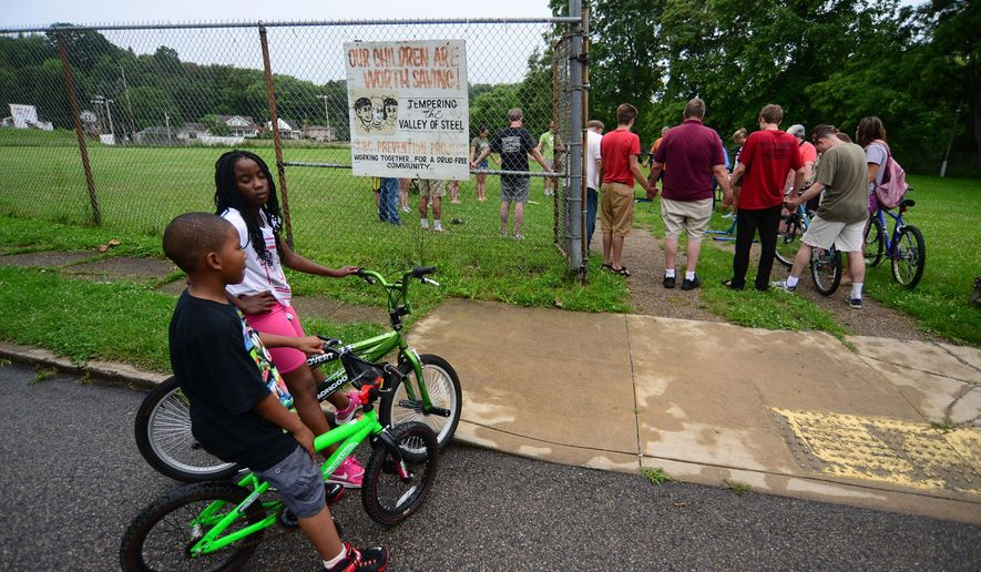 ADVANCE FOR SATURDAY, SEPT. 19, 2015 - In this June 25, 2015, photo, 8-year-old Jaden Parker, foreground, and 10-year-old Angel Henry wait for members of six area churches to finish praying before the volunteers repair children's bicycles in Aliquippa, Pa. Since 1987, the city of Aliquippa has been designated as a distressed municipality under the state's Act 47 recovery program - one of 29 municipalities assisted by the program - and within five years, city officials hope to join nine municipalities that exited the program. (Lucy Schaly/Beaver County Times via AP) MANDATORY CREDIT