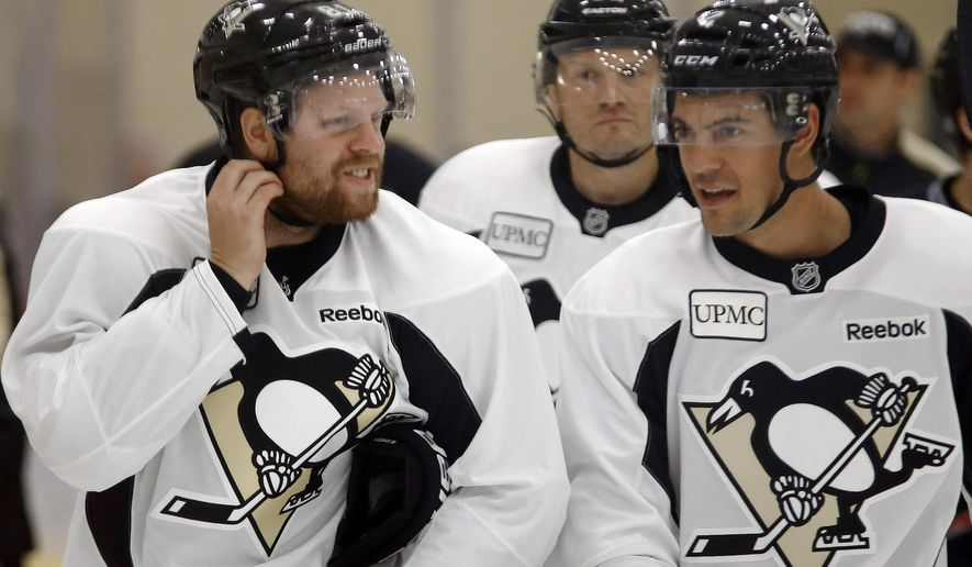 Pittsburgh Penguins' Phil Kessel, left, skates with Adam Clendening, right, and Sergei Gonchar, center, as they warm up during NHL hockey training camp, Friday, Sept. 18, 2015, in Cranberry Township, Pa. (AP Photo/Keith Srakocic)