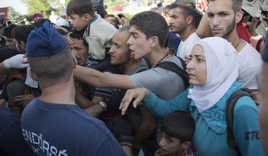 Migrants board a bus in Baranjsko Petrovo Selo, at the Hungarian border, northeast Croatia, Friday, Sept. 18, 2015. Croatia has sent buses full of migrants to Hungary just hours after the country's prime minister said it could not cope with the influx. But Hungarian police met the convoy of 19 buses in the border area and refused to let them cross in. (AP Photo/Darko Bandic)