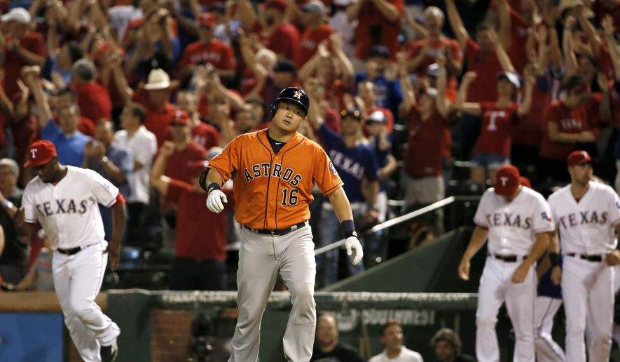 Houston Astros' Hank Conger jogs back to the dugout after grounding out duriong the ninth inning of a baseball game as the Texas Rangers come onto the field to celebrate their 8-2 win Thursday, Sept. 17, 2015, in Arlington, Texas. (AP Photo/Tony Gutierrez)