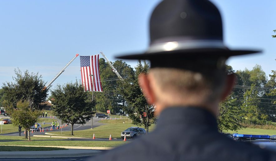 An officer from the Tompkinsville, Ky. police department watches as an American flag waives over the entrance to the Severns Valley Baptist Church before funeral services for Kentucky State Police Trooper Joseph Cameron Ponder in Elizabethtown, Ky., Friday, Sept. 18, 2015.  Ponder died Sunday night after being shot by a man he had stopped for speeding in western Kentucky.  (AP Photo/Timothy D. Easley)
