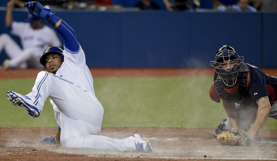 Toronto Blue Jays' Edwin Encarnacion, left, slide safely at home plate past Boston Red Sox catcher Blake Swihart during the fourth inning of a baseball game Friday, Sept. 18, 2015, in Toronto. (Nathan Denette/The Canadian Press via AP)
