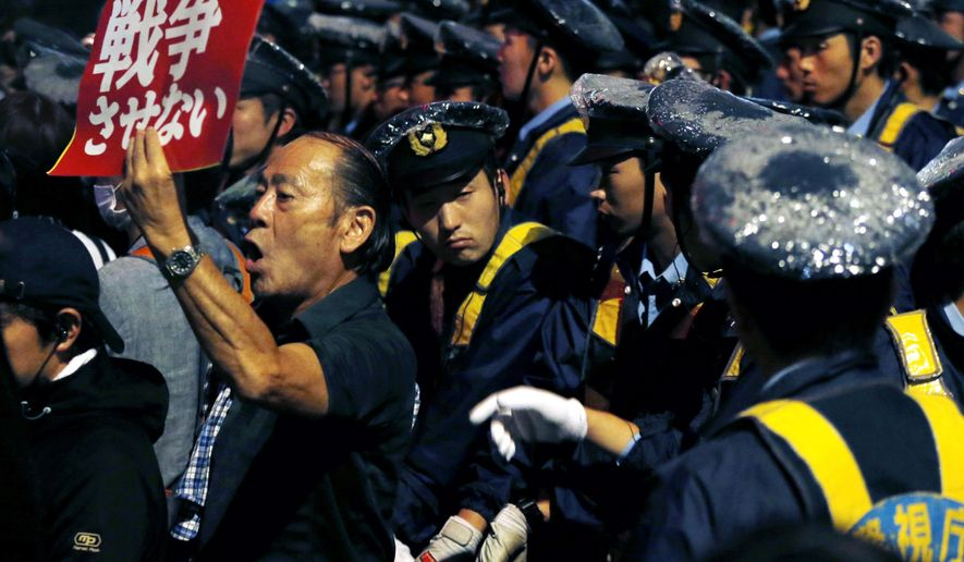 """A protester shouts slogans, surrounded by police officers, during a rally against Japanese government in front of the parliament building in Tokyo, Friday, Sept. 18, 2015. Japan's parliament is moving toward final approval of legislation that would loosen post-World War II constraints placed on its military, an issue that has sparked sizeable street protests and raised fundamental questions about whether the nation needs to shift away from its pacifist ways to face growing security challenges. The placard reads: """"No war."""" (AP Photo/Shuji Kajiyama)"""