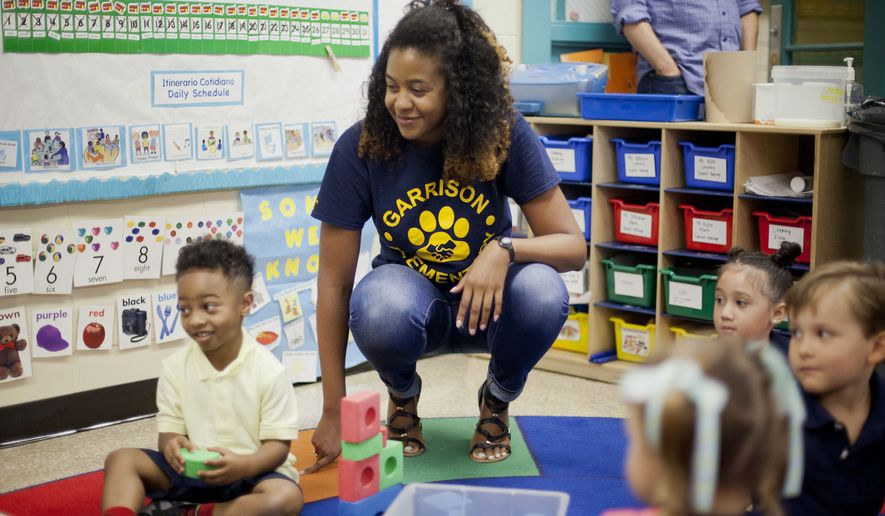 In this photo taken Aug. 28, 2015, Epernay Kyles, center, Pre-K teacher at Garrison Elementary in the Logan Circle neighborhood in Northwest Washington, meets with her students on the first day of classes. Millions of children are heading back to school after summer vacation. Many are excited, some anxious, and millions are still waiting for the results of the new tests they took last spring aligned to the Common Core academic standards. (AP Photo/Pablo Martinez Monsivais)