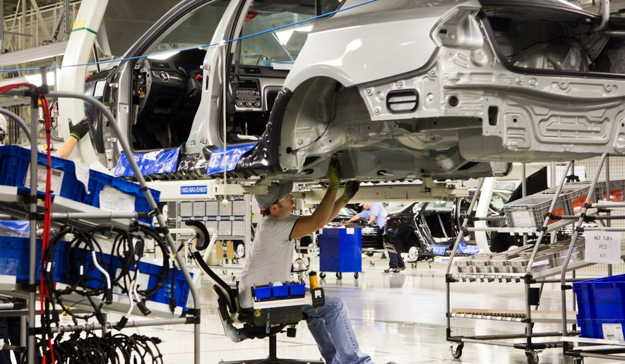 An employee works on a Passat sedan at the Volkswagen plant in Chattanooga, Tennessee, on July 31, 2012. (Associated Press) **FILE**