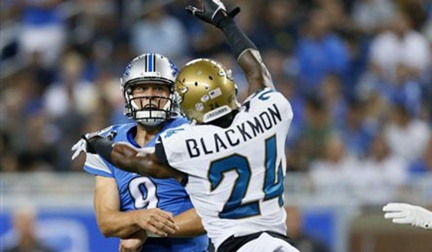 Jacksonville Jaguars cornerback Will Blackmon (24) pressures Detroit Lions quarterback Matthew Stafford (9) in the first half of a preseason NFL football game at Ford Field in Detroit, Friday, Aug. 22, 2014. (AP Photo/Rick Osentoski)