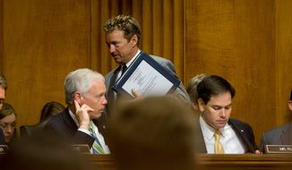 Sen. Rand Paul (center), Kentucky Republican and 2016 presidential candidate, arrives on Capitol Hill in Washington on April 14, 2015, for a Senate Foreign Relations Committee meeting to debate and vote on the Iran Nuclear Agreement Review Act of 2015. Sen. Marco Rubio, Florida Republican and fellow presidential candidate, is at right, and committee member Ron Johnson, Wisconsin Republican is at left. (Associated Press) **FILE**