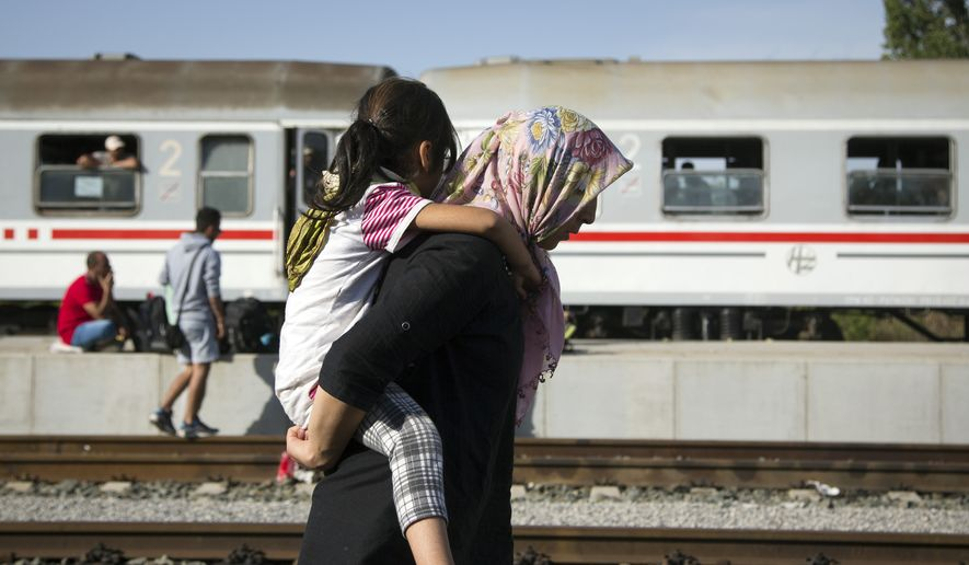 A refugee woman carries a child at a train station in Beli Manastir, near the Hungarian border, in northeast Croatia, early Friday, Sept. 18, 2015. Croatian police say some 13,300 migrants have entered the country from Serbia since the first groups started arriving more than two days ago. (AP Photo/Darko Bandic)