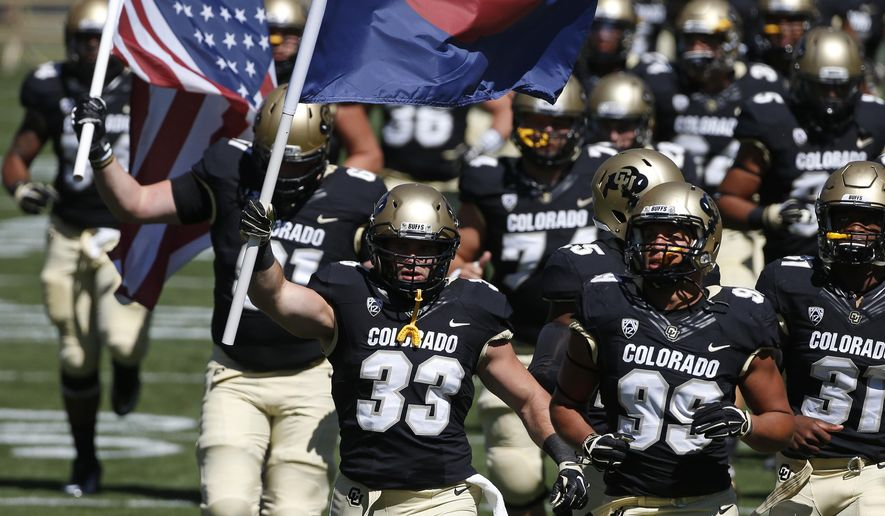"""In this Sept. 12, 2015 photo, Colorado fullback Jordan Murphy, front left, carries a Colorado state flag as he runs on to the field with teammates before the start of an NCAA college football game against Massachusetts, in Boulder, Colo. On July 20, 2012, Murphy was present at the showing of the Batman movie """"The Dark Knight Rises,"""" when James Holmes opened fire, murdering 12 people and wounding 70. Murphy escaped by crawling on the floor before dashing toward the exit, a bullet flying by his head and lodging in the drywall. (AP Photo/Brennan Linsley)"""