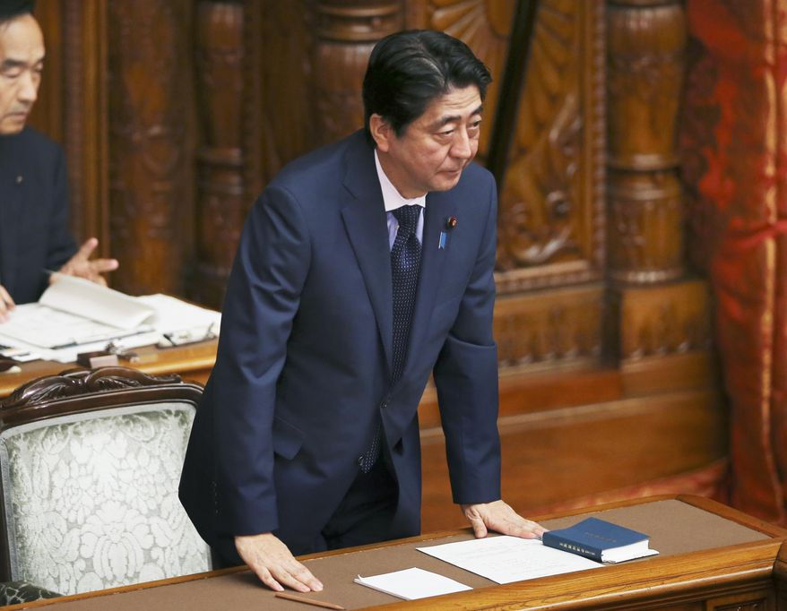 Japanese Prime Minister Shinzo Abe acknowledges after a censure motion against him filed by an opposition party was rejected during the upper house plenary diet session in Tokyo Friday, Sept. 18, 2015. The censure motion was filed by the opposition to block contentious security bills that Abe's ruling party is eager to get final approval by the upper house. The bills would ease restrictions on what the military can do, a highly sensitive issue in a country where many take pride in the postwar pacifist constitution. (AP Photo/Koji Sasahara)