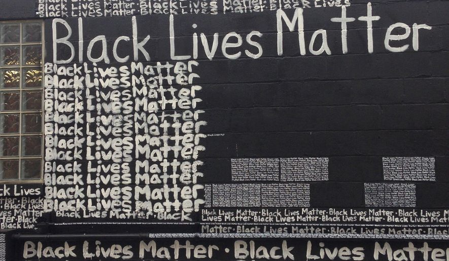 """Black Lives Matter"" is painted repeatedly on the exterior wall behind the N'Namdi Center for Contemporary Art, Friday, Sept. 18, 2015. in Detroit. Renda Writer, a white muralist from Miami, is expressing his support for the ""Black Lives Matter"" movement one word at a time on the art gallery wall. (AP Photo/Corey Williams)"