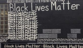 """""""Black Lives Matter"""" is painted repeatedly on the exterior wall behind the N'Namdi Center for Contemporary Art, Friday, Sept. 18, 2015. in Detroit. Renda Writer, a white muralist from Miami, is expressing his support for the """"Black Lives Matter"""" movement one word at a time on the art gallery wall. (AP Photo/Corey Williams)"""