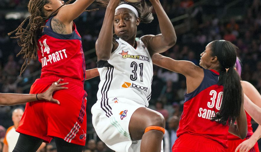 New York Liberty's Tina Charles pulls down a rebound past the Washington Mystics' Tierra Ruffin-Pratt (14) and LaToya Sanders (30) in the first half of game one of a WNBA Eastern Conference basketball playoff series, Friday, Sept. 18, 2015 at Madison Square Garden in New York. (AP Photo/Craig Ruttle)