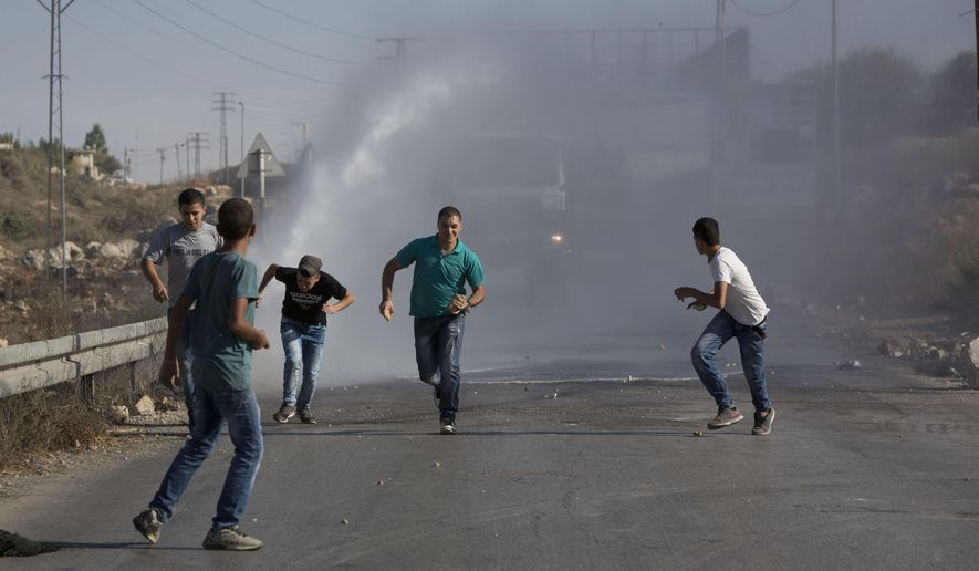 Palestinians run as Israeli troops use a water canon to disperse protesters during clashes in Jalazoun refugee camp, near the West Bank city of Ramallah, Friday, Sept. 18, 2015. Palestinian protesters continued clashing with Israeli security forces on Friday in various parts of the West Bank and east Jerusalem. (AP Photo/Majdi Mohammed) ** FILE **