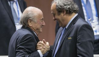 FILE - In this Friday, May 29, 2015 file photo, FIFA president Sepp Blatter after his election as President, left, is greeted by UEFA President Michel Platini, right, at the Hallenstadion in Zurich, Switzerland. At the start of his seventh decade and his third term as UEFA president, Michel Platini still seems to prefer to do much of his talking on the pitch despite being the most powerful figure in European football and the favorite to be installed as Sepp Blatter's FIFA successor in February 2016. (Patrick B. Kraemer/Keystone via AP, File)