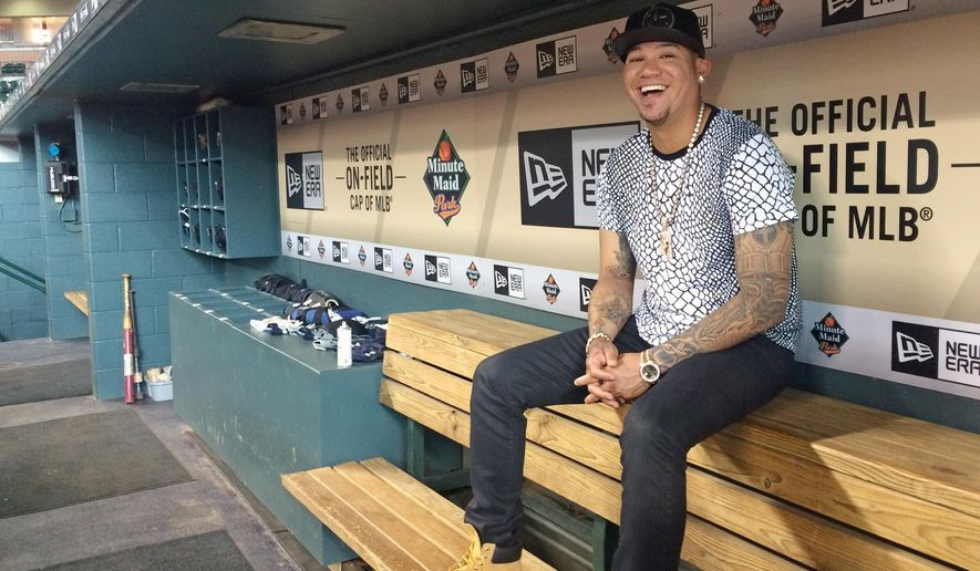 In this photo taken Tuesday, Sept. 1, 2015, Seattle Mariners ace Felix Hernandez smiles as he discusses his style and love of fashion, in the visiting team dugout at Minute Maid Park in Houston. Hernandez has a wardrobe befitting his royal nickname. King Felix dominates on the mound and his fashion rules off of it. The 29-year-old has painstakingly cultivated his style over 11 major league seasons and revels in discussing the intricacies of his look. (AP Photo/Kristie Rieken)
