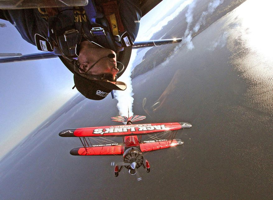 In this July 24, 2014 photo, which is the winner of the Reid Blackburn Memorial Award in the 2015 AP Northwest Photo Contest, Air National Guard aerobatic pilot Lt. Col. John Klatt, top, flies upside down over Elliott Bay, near Seattle as aerobatic pilot Jeff Boerboon, flies in formation below him. The pair were preparing for a performance at the annual Seafair Air Show. (Greg Gilbert/The Seattle Times via AP) SEATTLE OUT; USA TODAY OUT; MAGS OUT; TELEVISION OUT; NO SALES; MANDATORY CREDIT TO BOTH THE SEATTLE TIMES AND THE PHOTOGRAPHER