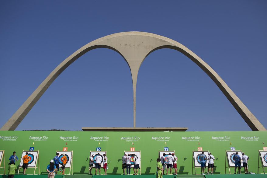 In this Tuesday, Sept. 15, 2015 photo, archers check the targets during the first day of the archery test event for the Rio 2016 Olympic Games at the Sambadrome in Rio de Janeiro, Brazil. Rio's Olympics next year should be a tour guide's delight with many of its most famous landmarks transformed for two weeks into sports venues for South America's first Games. The Sambadrome, home of the city's raucous Carnival parade, has been transformed into a venue for archery and the start and finish of the marathon. (AP Photo/Felipe Dana)