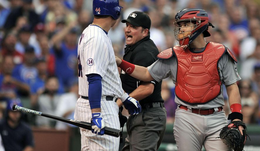 Chicago Cubs' Anthony Rizzo (44), argues with home plate umpire Dan Bellino after being hit by a pitch while St. Louis Cardinals catcher Tony Cruz (48), holds Rizzo back from charging the mound during the seventh inning of a baseball game Friday, Sept. 18, 2015 in Chicago. Chicago won 8-3. (AP Photo/Paul Beaty)