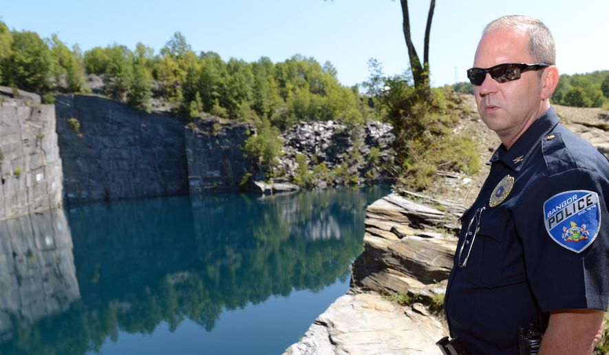 """ADVANCE FOR SATURDAY, SEPT. 19, 2015, - In this photo taken Tuesday, Aug. 25, 2015, Bangor, Pa., Police Chief Scott Felchock gives a tour of a Bangor quarry known as Seven Slopes of Slate quarry, where people frequently attempt to swim and 19 people were cited for trespassing the previous weekend. Although divers flock to a cliff about 120 feet above the water, water temperatures below the quarry's surface vary dramatically even in midsummer, posing risks of """"cold shock,"""" hypothermia and drowning as temperatures dip from the 70s at the surface to the 50s just 15 feet below. (Emily Paine/The Morning Call via AP) THE EXPRESS-TIMES OUT; WFMZ OUT; MANDATORY CREDIT"""
