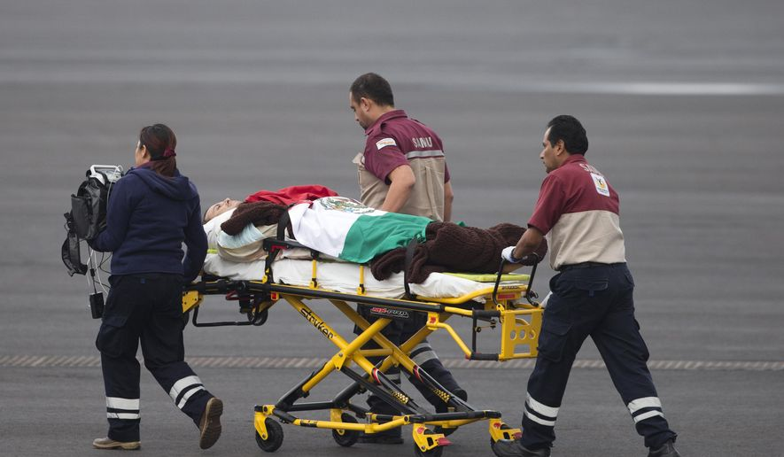 A Mexican man wounded in an attack by the Egyptian army while traveling in Egypt, is draped in a Mexican flag as he's transferred from the return flight to a waiting helicopter at the presidential hangar of Benito Juarez International Airport in Mexico City, Friday, Sept. 18, 2015.  Eight other Mexicans died Sunday when Egyptian forces hunting militants mistakenly attacked their convoy in the western desert. (AP Photo/Rebecca Blackwell)