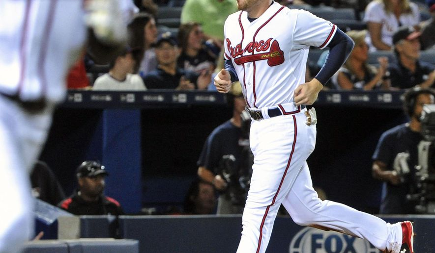 Atlanta Braves' Freddie Freeman approaches home to score on a single to center field by Cameron Maybin, left, during the fourth inning of a baseball game Friday, Sept. 18, 2015, in Atlanta. (AP Photo/John Amis)