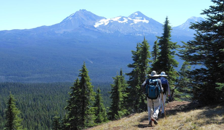 In this Sept. 9, 2015 photo, with the Three Sisters in the background, hikers make their way along the summit of Scott Mountain near McKenzie Pass, Ore. Central Oregon is home to so many inviting trails it can be downright daunting to determine the best option for a day hike. (Mark Morical/The Bulletin via AP) MANDATORY CREDIT