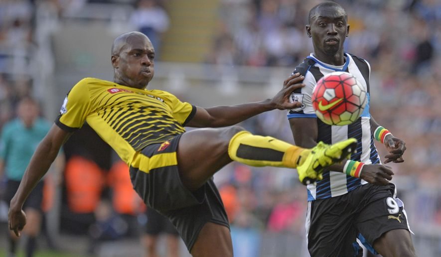 Newcastle's Papiss Cisse, right, and Watford's Allan Nyom battle for the ball during their English  Premier League match at St James' Park, Newcastle, England Saturday Sept. 19, 2015. (Owen Humphreys/PA via AP) UNITED KINGDOM OUT