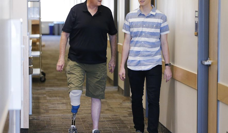 BYU student Jacob Hatch walks with his father Bryant on campus in Provo, Utah, Wednesday, Sept. 9, 2015. Bryant contracted MRSA, a bacteria that causes serious disease and death, and had to have one leg amputated. (Jeffrey D. Allred/The Deseret News via AP)  SALT LAKE TRIBUNE OUT; MAGS OUT; MANDATORY CREDIT