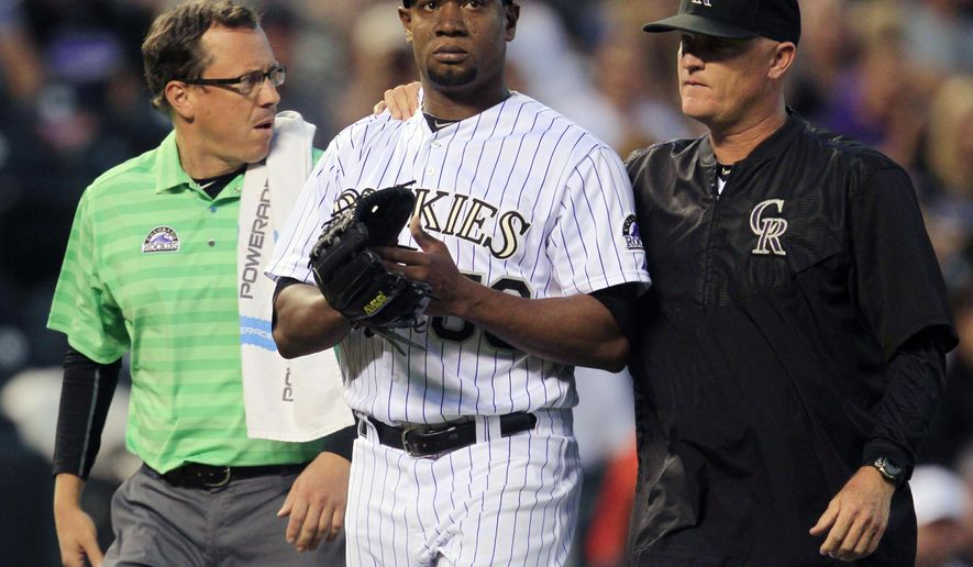 Colorado Rockies assistant trainer Scott Gehret, left, escorts starting pitcher Yohan Flande, center, from the game with pitching coach Stephen Foster, after Flande was hit in the left leg by San Diego Padres batter Jedd Gyorko's line drive in the third inning of a baseball game in Denver on Saturday, Sept. 19, 2015.(AP Photo/Joe Mahoney)