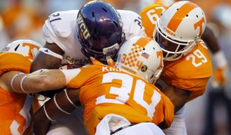 Western Carolina running back Detrez Newsome (21) is tackled by Tennessee linebacker Darrin Kirkland Jr. (34), defensive back Evan Berry (29) and defensive lineman Kyle Phillips (5) during the first half of an NCAA college football game Saturday, Sept. 19, 2015, in Knoxville, Tenn. (AP Photo/Wade Payne)