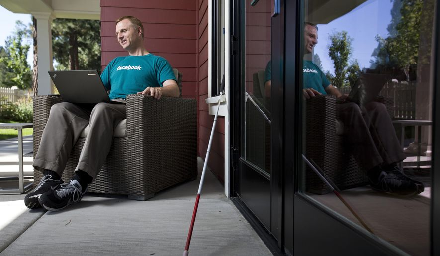 In this Sept. 9, 2015 photo, Matt King works on his laptop at his home in Bend, Ore. King, who is blind, started working for Facebook at the company's headquarters in June as an accessibility engineer. (Joe Kline/The Bulletin via AP) MANDATORY CREDIT
