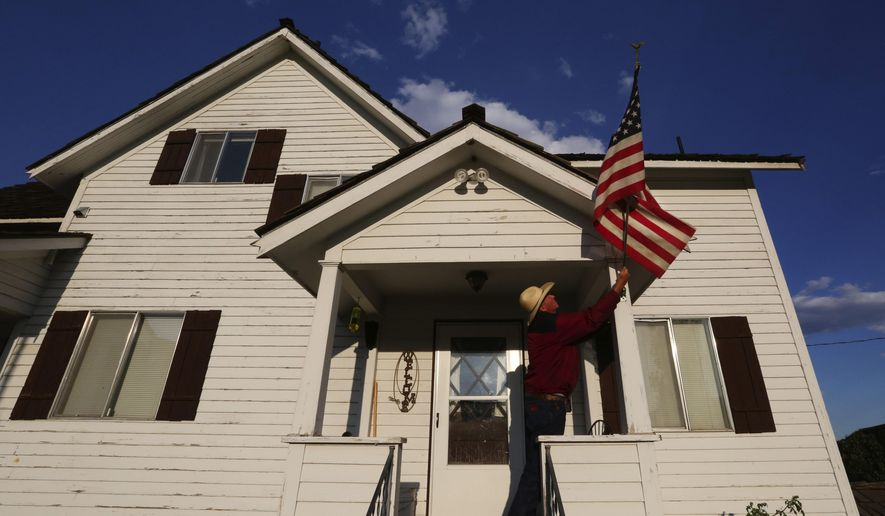 This Sept. 2, 2015 photo shows Rod Haeberle adjusting the American flag outside his home, which was saved from the fires by volunteer firefighters from District 9, Okanogan County. They worked for days and saved all but one home in their district. (Alan Berner/The Seattle Times via AP) OUTS: SEATTLE OUT, USA TODAY OUT, MAGAZINES OUT, TELEVISION OUT, SALES OUT. MANDATORY CREDIT TO: ALAN BERNER  / THE SEATTLE TIMES