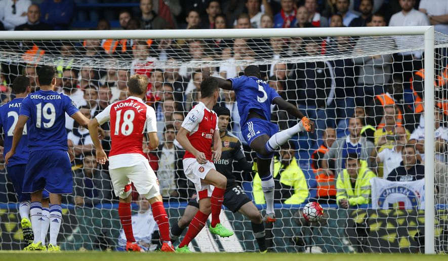 Chelsea's Kurt Zouma, right heads the Ball to score the opening goal during the English Premier League soccer match between Chelsea and Arsenal at Stamford Bridge stadium in London, Saturday, Sept. 19 2015. (AP Photo/Alastair Grant)