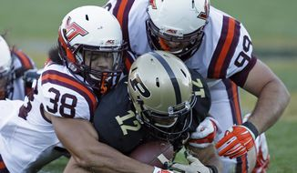 Purdue's Austin Appleby (12) recovers his fumble while being tackled by Virginia Tech's Joe Koshuta (38) and Vinny Mihota (99) during the second half of an NCAA college football game Saturday, Sept. 19, 2015 in West Lafayette, Ind. Virginia Tech won the game 51-24. (AP Photo/Darron Cummings)