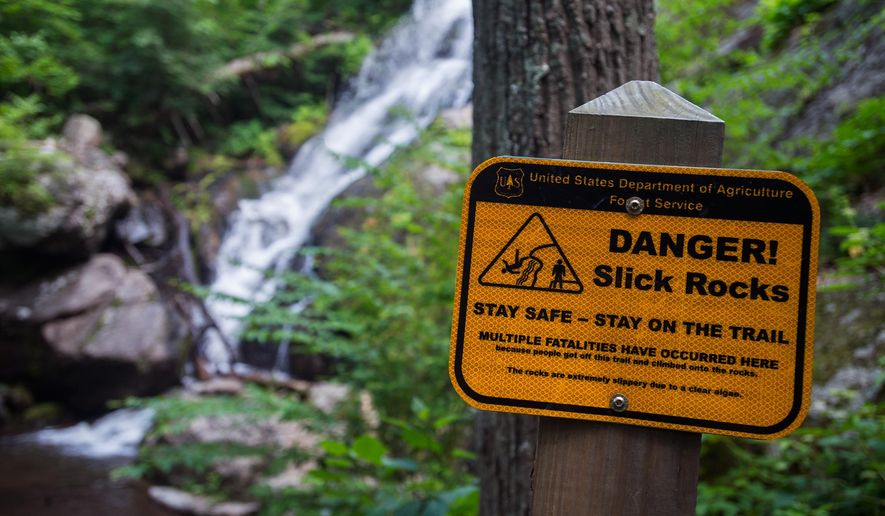 This June 7, 2015 photo, signs line the trail at Crabtree Falls, warning visitors not to stray from the path due to slippery rocks in Nelson County, Va.  At least 30 people have died at Crabtree Falls in Nelson County since the U.S. Forest Service began tracking the incidents in 1982.  (Autumn Parry/News & Daily Advance via AP) MANDATORY CREDIT