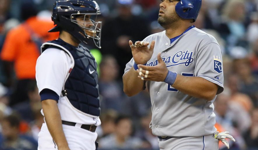 Kansas City Royals' Kendrys Morales, right, scores past Detroit Tigers catcher Alex Avila after hitting a solo home run during the second inning of a baseball game at Comerica Park, Saturday, Sept. 19, 2015, in Detroit. (AP Photo/Duane Burleson)