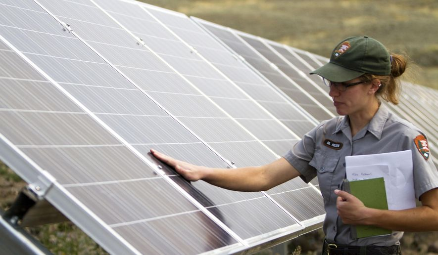 In this Thursday, Aug. 27, 2015 photo, Molly Nelson talks about a solar power array that is part of sustainability improvements at the Lamar Buffalo Ranch in Yellowstone National Park, Wyo. (Ryan Jones/Jackson Hole News&Guide via AP)
