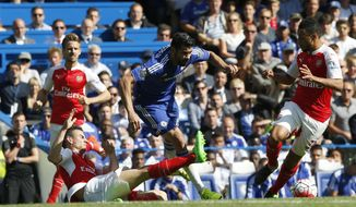 Chelsea's Diego Costa, centre is brought down and fouled by Arsenal's Laurent Koscielny during the English Premier League soccer match between Chelsea and Arsenal at Stamford Bridge stadium in London, Saturday, Sept. 19 2015. (AP Photo/Alastair Grant)